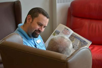 Cornerstone Carer reading to a resident
