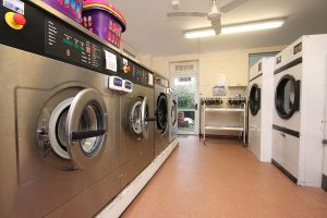 Cornerstone Specialist Nursing Home Laundry - row of industrial washing machines and dryers